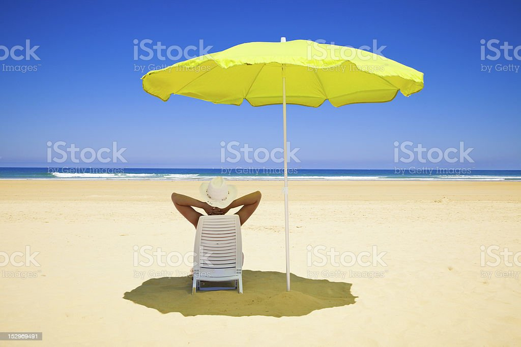 woman resting under a beach umbrella facing the seaside royalty-free stock photo