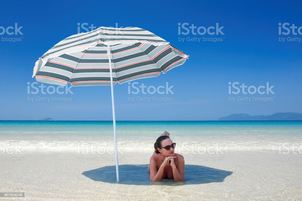 woman resting under a beach umbrella. stock photo