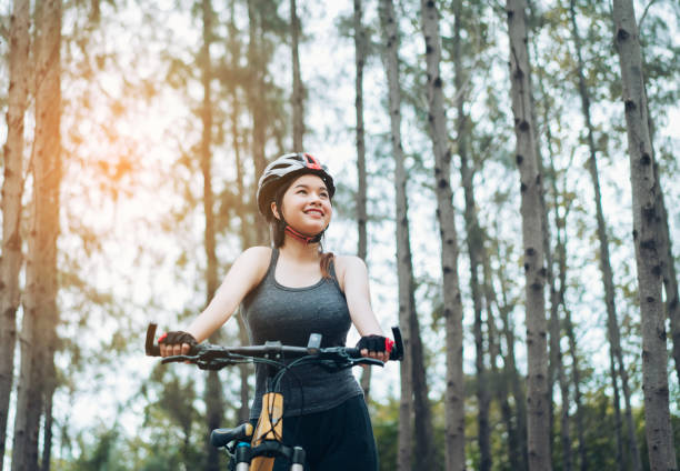 Woman resting with bicycle in the forest after ride workout her active activity fitness outdoor on autumn and summer healthy lifestyle,adventure travel trip. Woman resting with bicycle in the forest after ride workout her active activity fitness outdoor on autumn and summer healthy lifestyle,adventure travel trip. female biker resting stock pictures, royalty-free photos & images