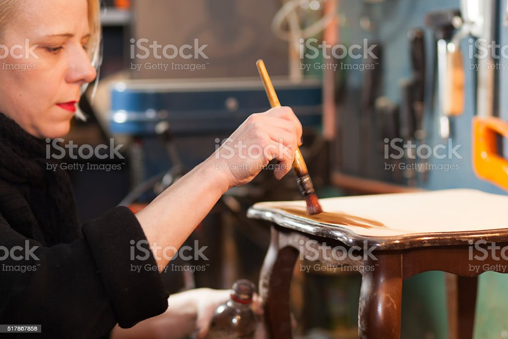 woman restoring furniture stock photo