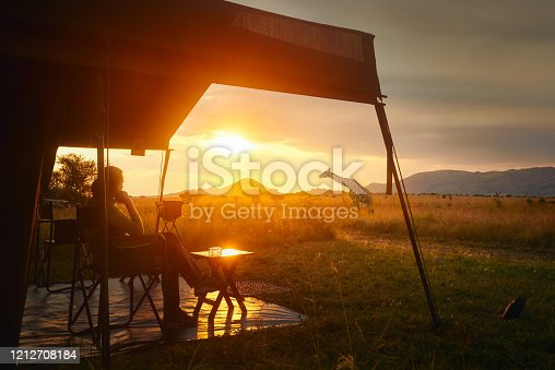 Woman rests after safari in luxury tent during sunset camping in the African savannah of Serengeti National Park, Tanzania. Woman Camping Tent Savanna Outdoors Concept