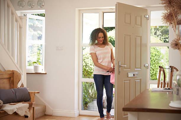 woman returning home and opening front door - llegada fotografías e imágenes de stock