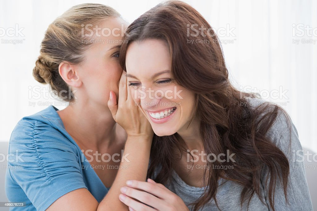 Woman revealing secret to her friend smiling stock photo