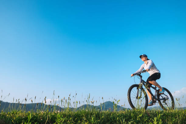 Woman ride a bike: summertime activity stock photo