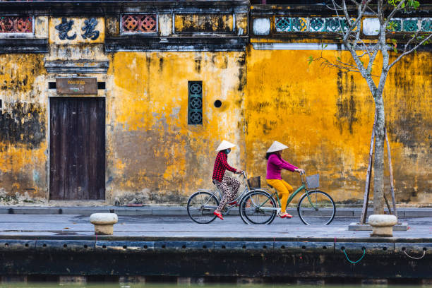 Woman ride bicycle in Hoi An stock photo