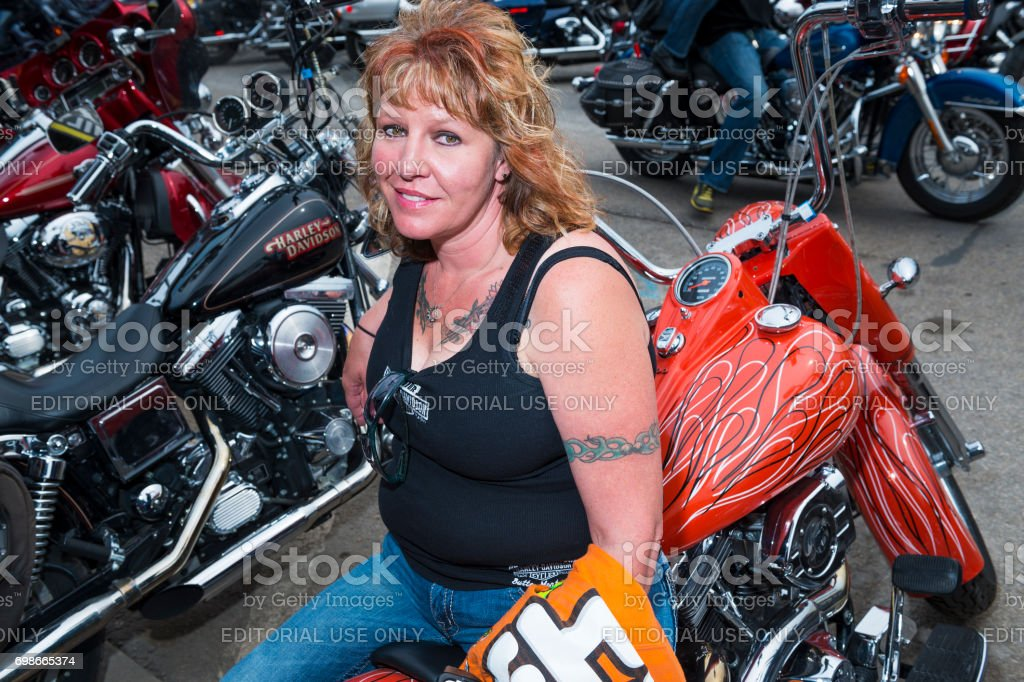 Woman Rider sitting on her bike in the city of Sturgis, in South Dakota, USA, during the annual Sturgis Motorcycle Rally stock photo