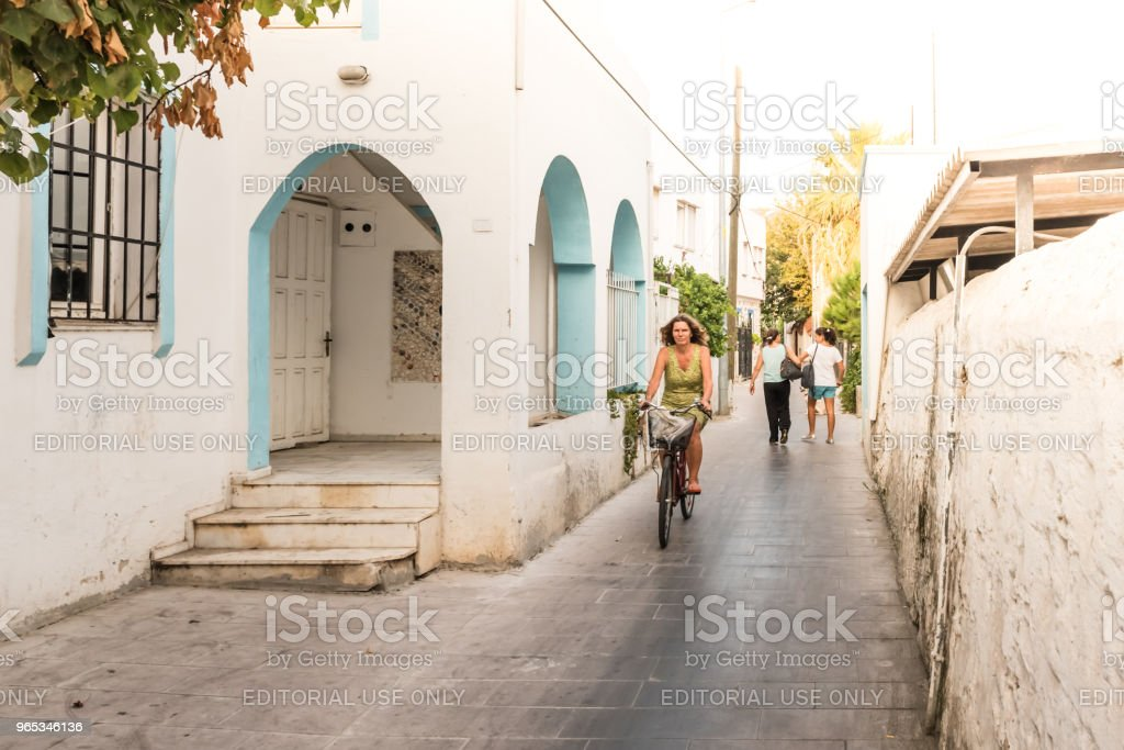 woman rides a bike at old narrow streets of Bodrum royalty-free stock photo