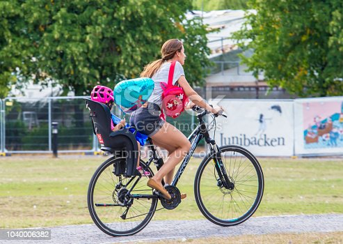 583973114istockphoto A woman rides a child on a bicycle 1040006382