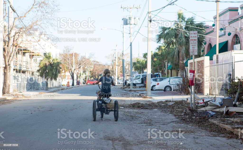 Woman rides a tricycle down a deserted street in Key West after a hurricane stock photo