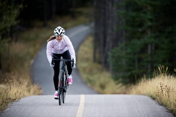eine frau fährt ihr rennrad entlang der trans canada trail-bikepath in der nähe von canmore, alberta, kanada im herbst. - straßentraining stock-fotos und bilder