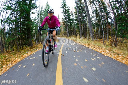 861018326 istock photo A woman rides her road bike along the Trans Canada Trail bikepath near Canmore, Alberta, Canada in the autumn. 864724432