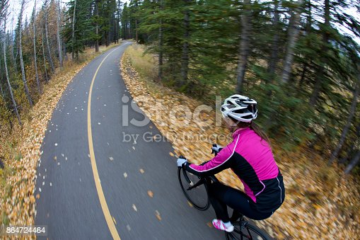861018326 istock photo A woman rides her road bike along the Trans Canada Trail bikepath near Canmore, Alberta, Canada in the autumn. 864724464