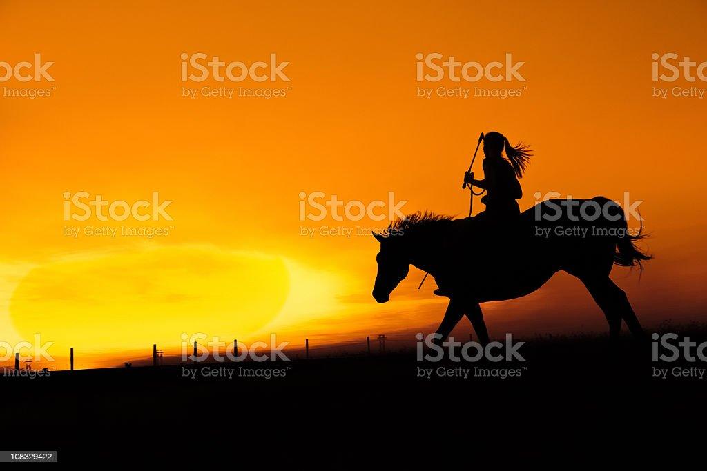 Woman Rides Hosreback Into The Sunset stock photo