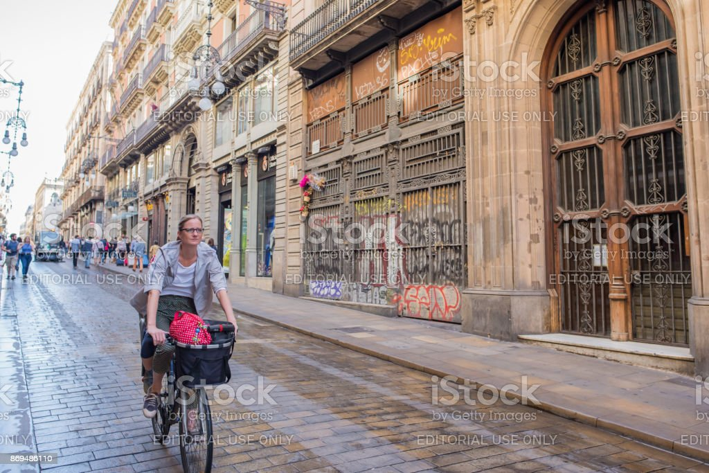 Woman riding a bicycle in Barcelona's Gothic Quarter stock photo