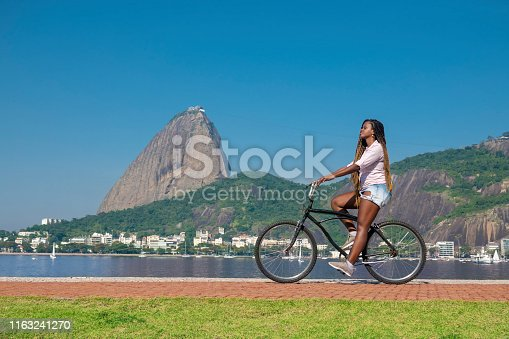 Beautiful black brazilian woman rides on the bike path in front of the Sugarloaf in Flamengo Park