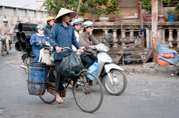 woman riding a bicycle in vietnam - motorbike, umbrella stock pictures, royalty-free photos & images