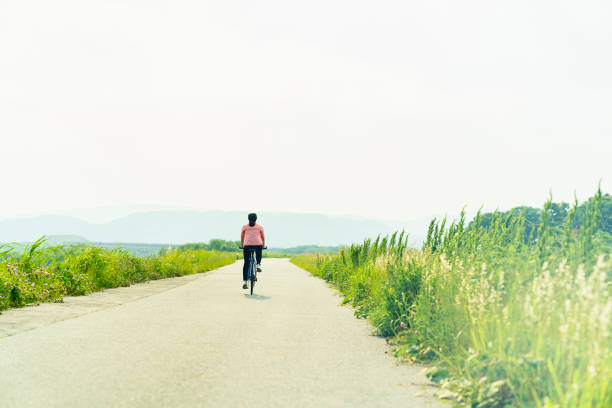 Woman riding a bicycle on a road stock photo