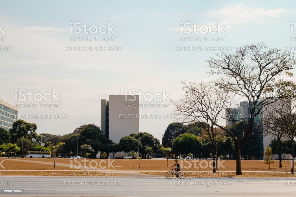 Brasilia, Brazil - August 14, 2016:  Woman riding a bike at the Monumental Axis in Brasilia with the Minister Offices on the back on a Sunday Afternoon. stock photo