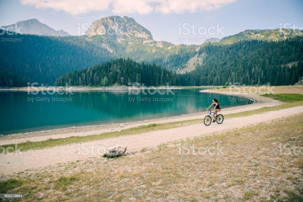 Woman riding a bike by the lake. stock photo