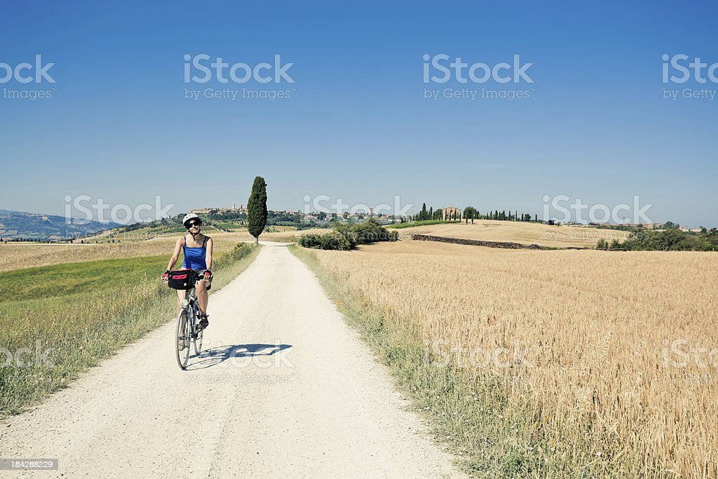 Woman Riding a Bike in the Countryside, Tuscany royalty-free stock photo
