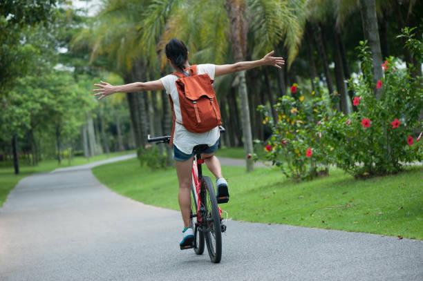 Frau mit dem Fahrrad auf sonnigen Park Trail mit ausgestreckten Armen – Foto