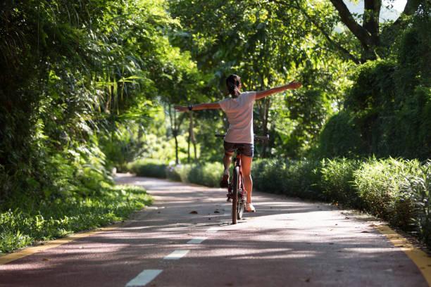 Frau fährt fahrradauf sonnigem Parkweg ohne Hand – Foto