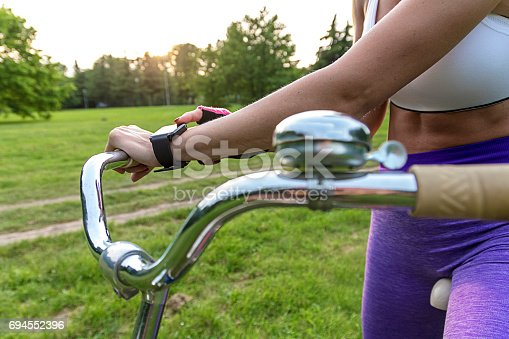 istock Woman riding a bike with a smartwatch heart rate monitor 694552396