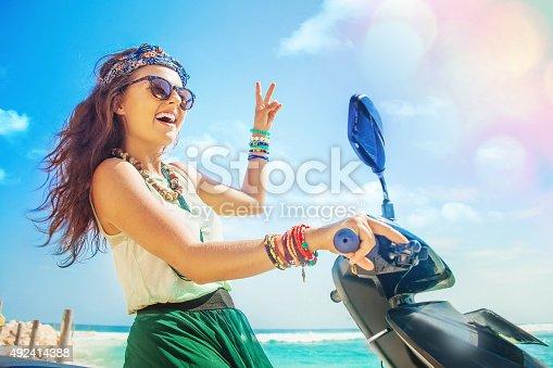 istock Woman riding a motorbike along beach 492414388