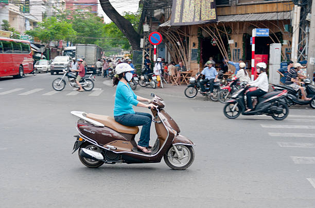 woman riding a motorcycle in hcmc, vietnam - motorbike, umbrella stock pictures, royalty-free photos & images