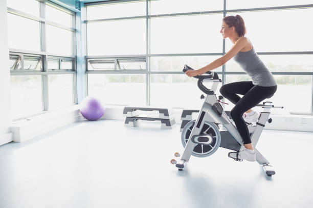 Woman riding an exercise bike Woman riding an exercise bike in gym exercise bike stock pictures, royalty-free photos & images
