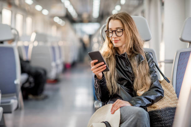Woman riding at the modern train Lifestyle portrait of a young businesswoman sitting with smart phone at the modern train passenger stock pictures, royalty-free photos & images