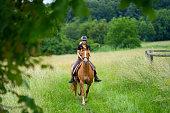 female rider riding beautiful sorrel colored horse outdoors in rural landscape green grassland with forest in background, view through trees