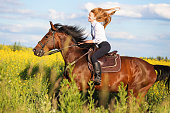 Woman riding bay horse among yellow flowers.