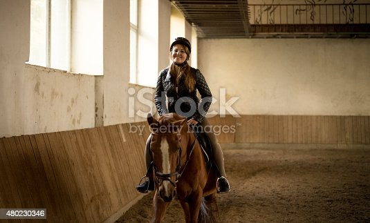 Portrait of woman riding beautiful brown horse at indoor manege