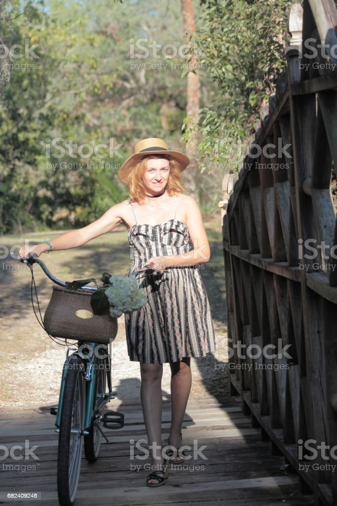 Woman riding bicycle in a tropical park. 免版稅 stock photo