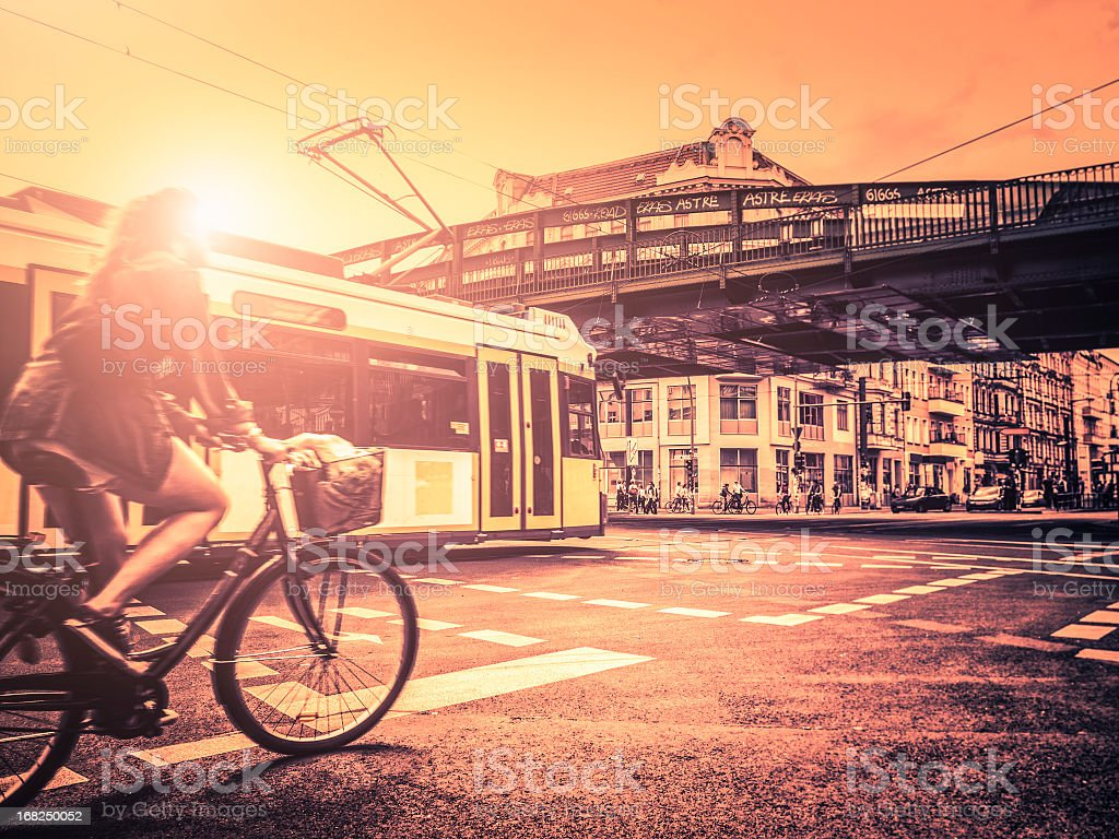 Woman riding bicycle in Berlin against tram at sunset royalty-free stock photo
