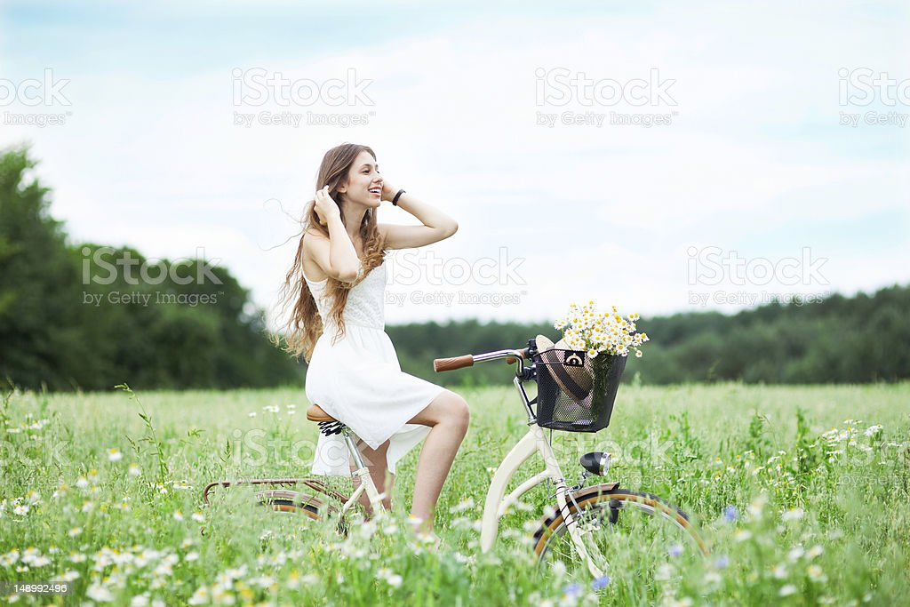 Woman riding bicycle in wildflower field royalty-free stock photo