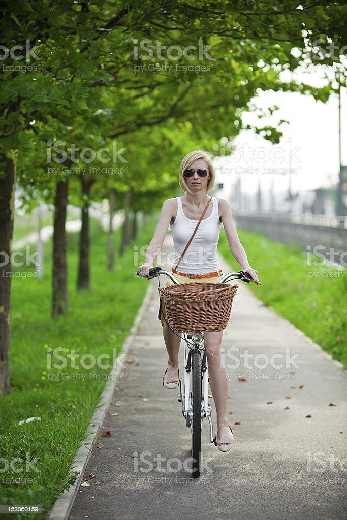 Woman riding bicycle on a bike path royalty-free stock photo