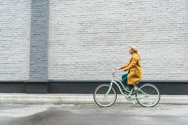 woman riding bicycle - cycling stock pictures, royalty-free photos & images