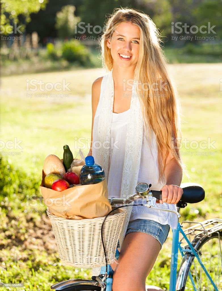 Woman Riding Bicycle With Groceries In Basket royalty-free stock photo