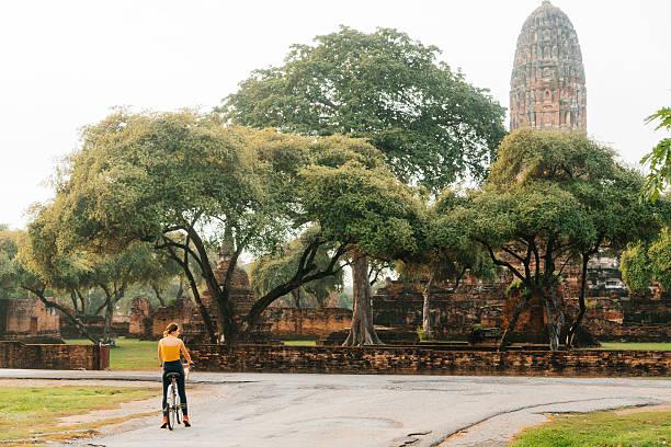 Woman riding bike near ancient Buddhist Temples stock photo