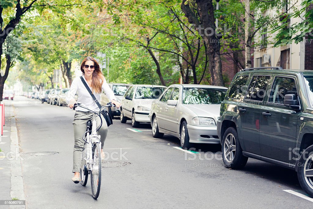 Woman riding electric bicycle stock photo