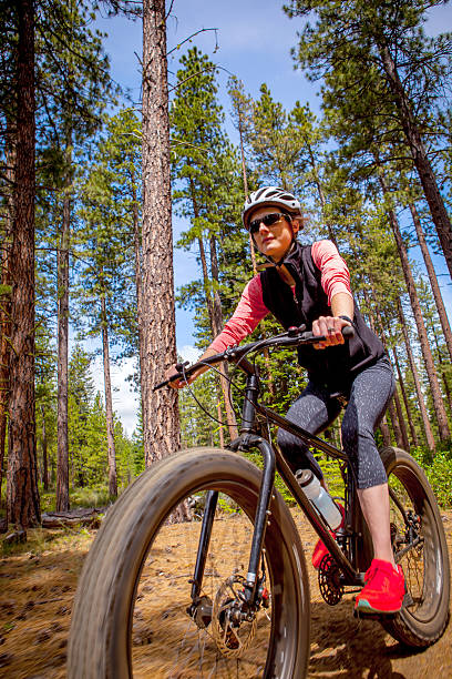 Woman riding her fatbike on a trail in Oregon stock photo