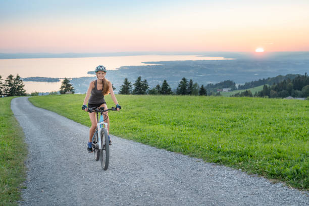 Woman riding her Mountain Bike up the famous Pfänder Mountain, Lake Constance (Bodensee) in back, Austria Woman riding her Mountainbike up the famous Pfänder Mountain, Lake Constance (Bodensee) in back, Austria. Bodensee stock pictures, royalty-free photos & images