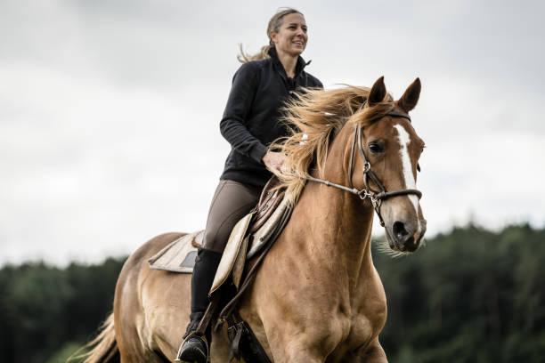 女性乗馬馬劇的な空 - 乗馬 ストックフォトと画像