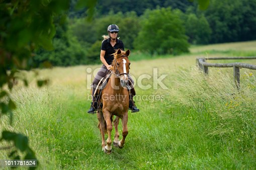 female rider galloping over green meadow on beautiful sorrel colored horse