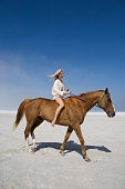 Full length side view of a female riding horse on beach