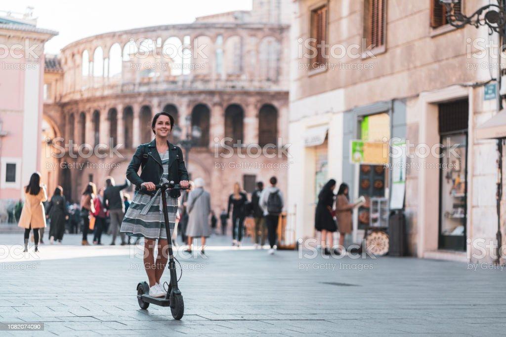 Woman riding motor scooter at Plaza de la Virgen against Valencia cathedral in Valencia - Foto stock royalty-free di Abbigliamento casual