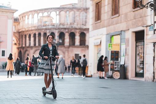 Woman Riding Motor Scooter At Plaza De La Virgen Against Valencia Cathedral In Valencia - Fotografie stock e altre immagini di Abbigliamento casual