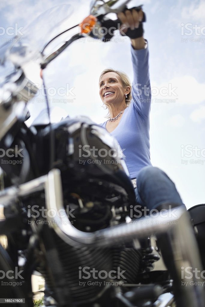 Woman Riding Motorcycle Against Cloud Sky royalty-free stock photo